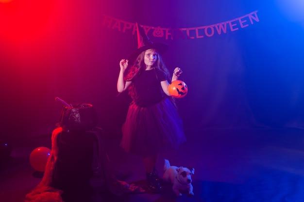 Lustiges kindermädchen im hexenkostüm für halloween mit kürbis-jack und hund