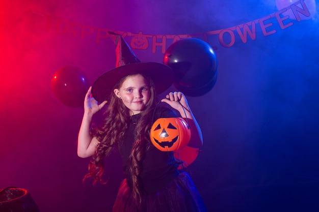 Lustiges kindermädchen im hexenkostüm für halloween mit kürbis jack
