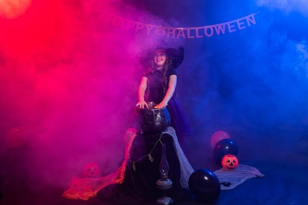 Lustiges kindermädchen im hexenkostüm für halloween mit kürbis jack.