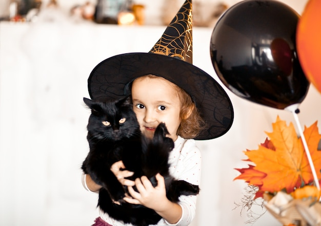 Lustiges kindermädchen im hexenkostüm für halloween mit schwarzer katze in den händen.