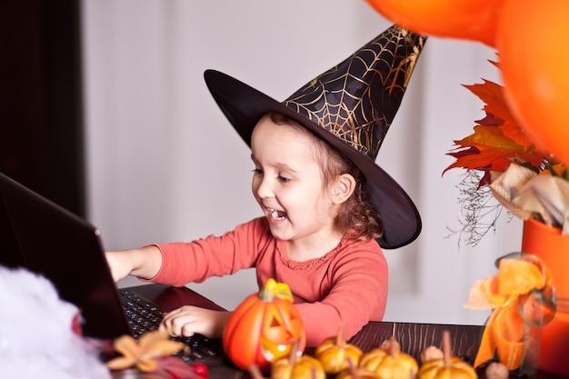 Lustiges kindermädchen im hexenkostüm für halloween unter verwendung eines digitalen tablet-laptop-notizbuchs. online-anruf freunde oder eltern.