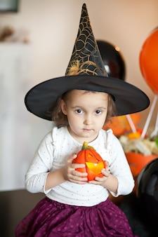 Lustiges kindermädchen im hexenkostüm für halloween.