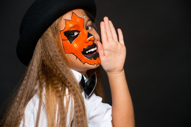 Lustiges kindermädchen im kürbiskostüm für halloween. halloween make-up. gesichtskunst.