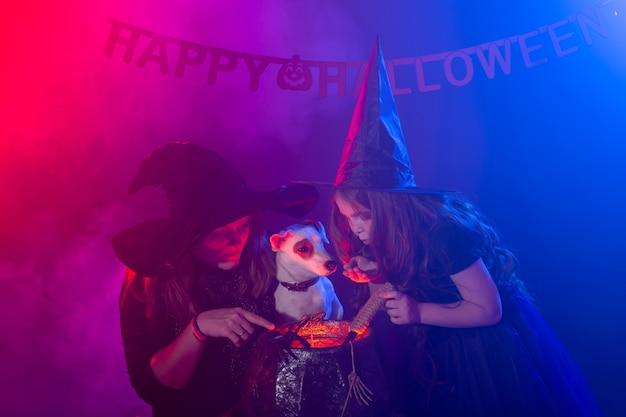Lustiges kindermädchen und -frau in den hexenkostümen für halloween mit dem hund, der magie macht.