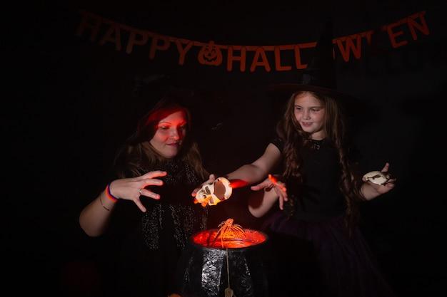 Lustiges kindermädchen und -frau in hexenkostümen für halloween, die magie machen.