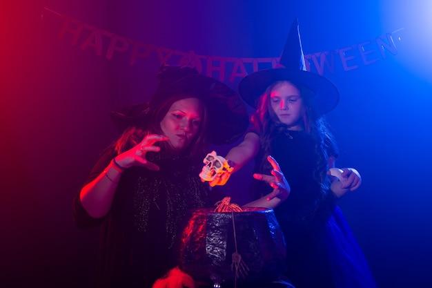 Lustiges kindermädchen und frau in hexenkostümen für halloween mit kürbis jack und hund