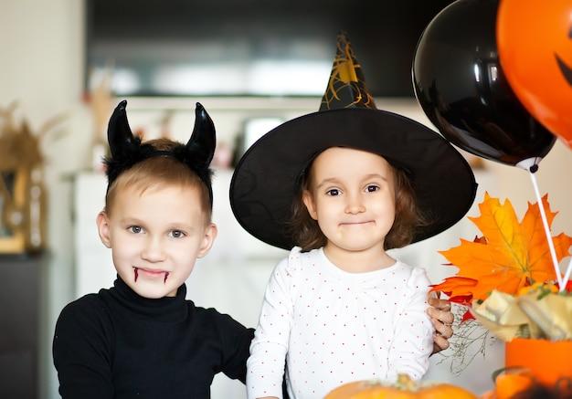Lustiges kindermädchen und jugendlich junge in hexen- und bösen kostümen für halloween-party