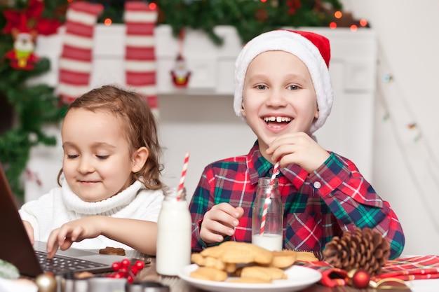 Lustiges kindermädchen und -junge in der weihnachtsmannmütze, die weihnachtsmilch trinkt, die kekse isst