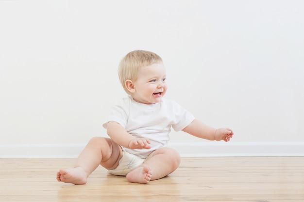 Lustiges kleines baby auf holzboden