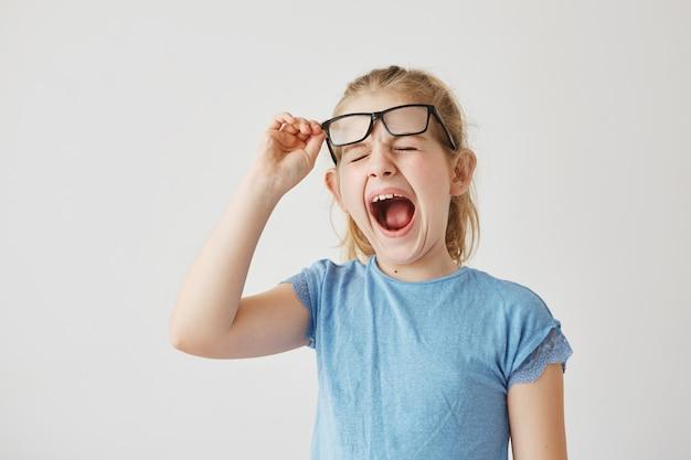 Lustiges kleines blondes mädchen mit hübschen blauen augen, die brille heben und mit geschlossenen augen im klassenzimmer gähnen, weil lange langweilige lektion.