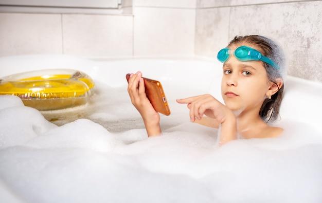 Lustiges kleines kaukasisches mädchen in der schwimmbrille surft das internet unter verwendung eines smartphones beim schwimmen im badezimmer mit schaum zu hause.