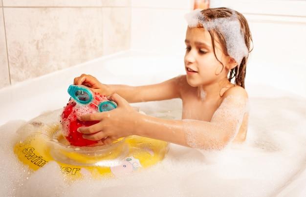 Lustiges kleines mädchen badet in einem bad mit schaum und spielt lebensrettenden ball