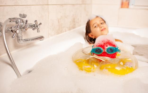 Lustiges kleines mädchen badet in einer badewanne mit schaum und spielt lebensrettenden ball und schwimmbrillen. kinderfreizeit zu hause konzept. exemplar