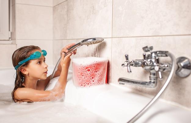 Lustiges kleines mädchen badet in einer badewanne und gießt wasser in den weißen schaum von der dusche.