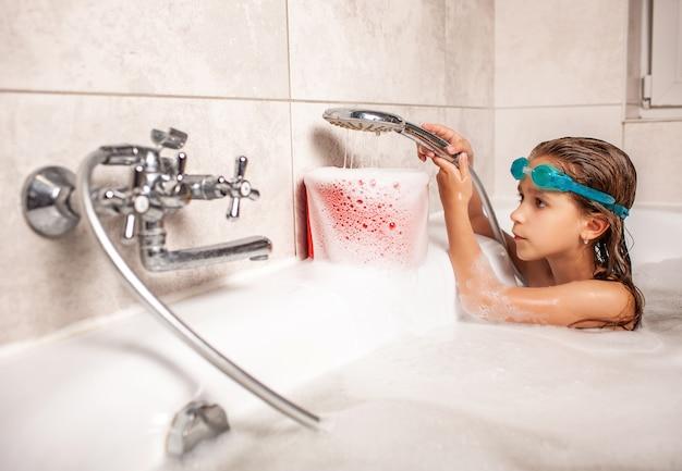 Lustiges kleines mädchen badet in einer badewanne und gießt wasser in den weißen schaum von der dusche