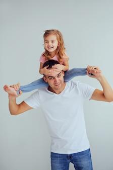 Lustiges kleines mädchen, das auf dem stutzen und dem lächeln ihres vaters sitzt. ein junger mann spielt mit einem kind