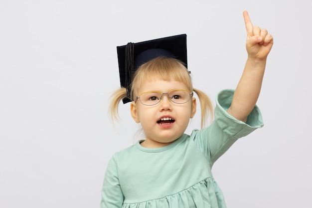 Lustiges kleines mädchen, das brillen trägt, ahmt einen lehrer gegen weißen hintergrund nach. kleiner student legte finger hoch blick in die kamera. schulkonzept. zurück zur schule