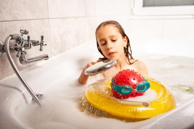 Lustiges kleines mädchen, das einen kopf duscht, der von einem ball gemacht wird und schutzbrille von der dusche schwimmt