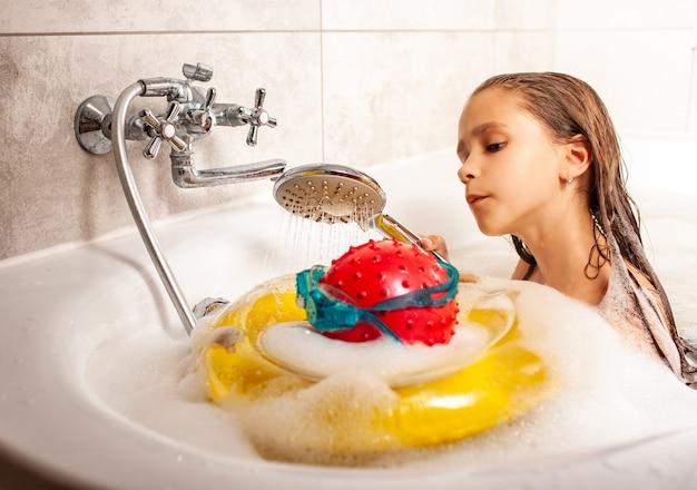 Lustiges kleines mädchen, das einen kopf duscht, der von einem ball und von der schwimmbrille gemacht wird