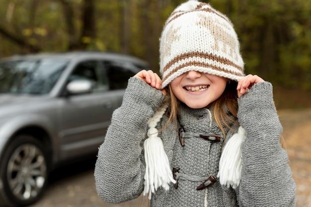 Lustiges kleines mädchen, das ihr gesicht mit winterhut bedeckt