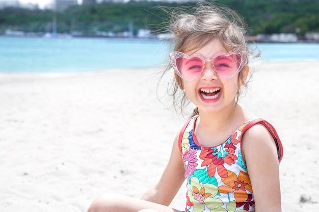 Lustiges kleines mädchen, das in der sonnenbrille aufwirft, die mit sand am strand spielt. sommerunterhaltung und erholung.