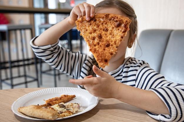 Lustiges kleines mädchen, das käsepizza zum mittagessen hautnah isst.