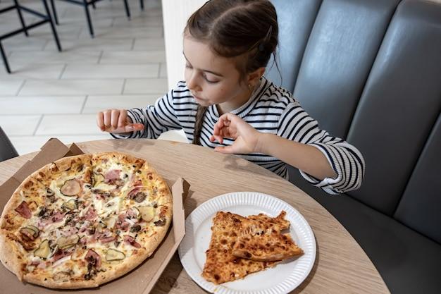 Lustiges kleines mädchen, das pizza in einem pappkarton zum mittagessen isst.