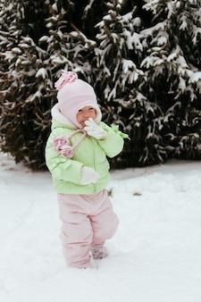 Lustiges kleines mädchen, das spaß im schönen winterpark während der schneefälle hat