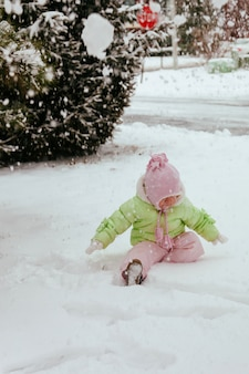 Lustiges kleines mädchen, das spaß im schönen winterpark während hat