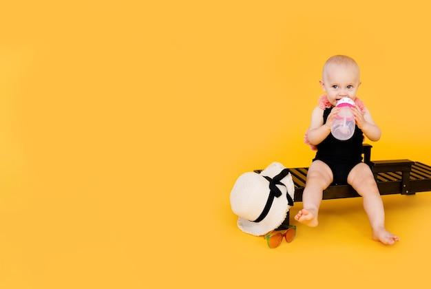 Lustiges kleines mädchen gekleidet in einem schwarzen und rosa badeanzug, großer hut, der auf hölzernem liegestuhl mit flasche wasser auf gelb sitzt