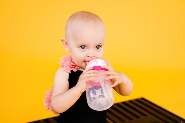 Lustiges kleines mädchen gekleidet in einem schwarzen und rosa badeanzug, großer hut, der auf hölzernem liegestuhl mit flasche wasser auf gelbem hintergrund sitzt. sommerferienkonzept.