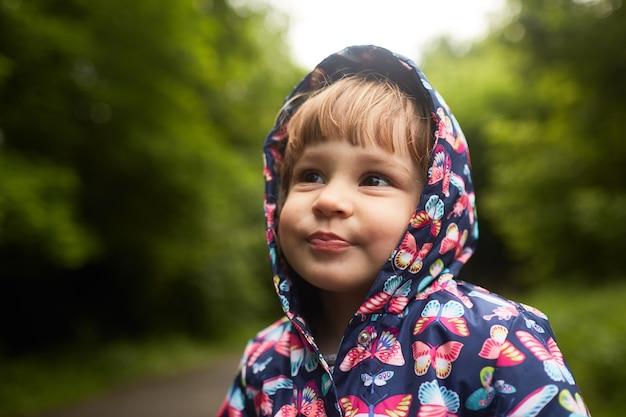 Lustiges kleines mädchen im regenmantel steht im grünen park