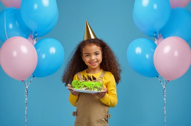 Lustiges kleines mädchen in der mütze hält geburtstagskuchen, blauer hintergrund. hübsches kind hat eine überraschung, eventfeier, ballondekoration bekommen
