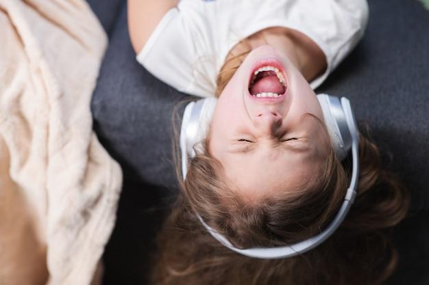 Lustiges kleines mädchen in drahtlosen kopfhörern tanzt singend und bewegt sich zum rhythmus. kleines mädchen mit kopfhörern. kind in kopfhörern. glückliches kleines mädchen, das musik mit kopfhörern hört.