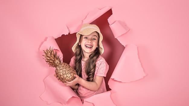 Lustiges kleines mädchen in einem strandhut und mit ananasgoldfarbe, auf einem farbigen rosa hintergrund, der aus dem loch im hintergrund herausschaut, studioaufnahme, raum für text
