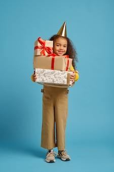 Lustiges kleines mädchen in mütze hält geburtstagsgeschenkbox mit roten bändern, blauer hintergrund. hübsches kind hat eine überraschung bekommen