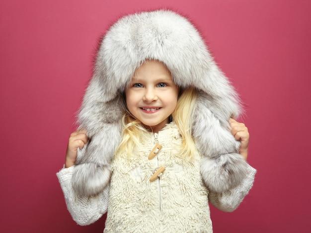 Lustiges kleines mädchen in warmer kleidung auf farboberfläche