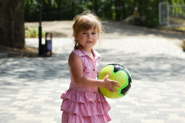 Lustiges kleines mädchen mit ball auf spielplatz im freien. junge süße sportlerin mädchen.