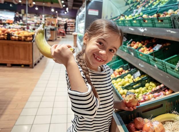 Lustiges kleines mädchen mit banane am supermarkt.