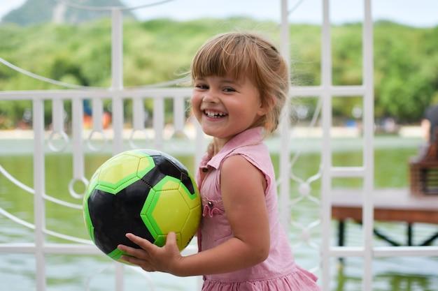 Lustiges kleines mädchen mit einem ball auf dem spielplatz im freien.
