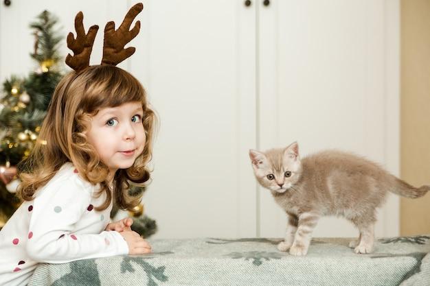 Lustiges kleines mädchen mit kleinem kätzchen. weihnachtsbaum