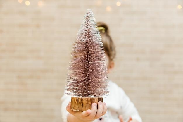 Lustiges kleines mädchen mit weihnachtsbaum. minimalistischer stil.