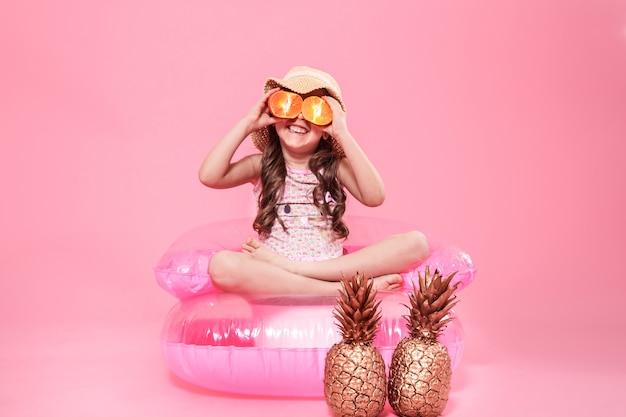 Lustiges kleines mädchen mit zitrusfrucht auf farbe