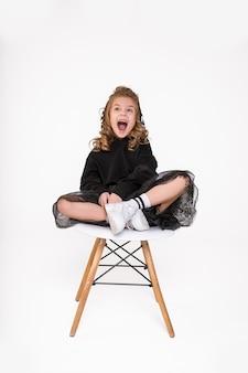 Lustiges kleines mädchen sitzen auf modischem stuhl auf weißem hintergrund im studio und schreien oder lachen laut. kinderemotionskonzept