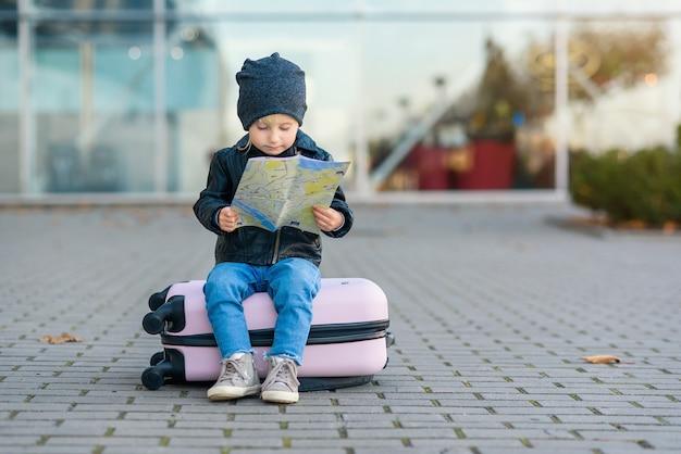 Lustiges kleines mädchen sitzt auf rosa koffer mit karte in den händen nahe dem flughafen.