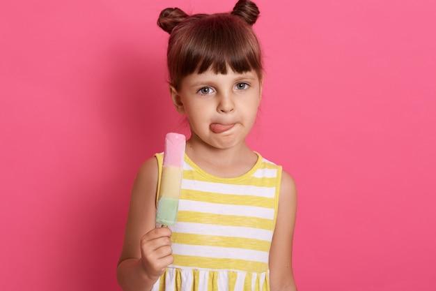 Lustiges kleines mädchen, während sie ihre lippen leckt, charmantes weibliches kind, das fruchtsorbet isst, isoliert über rosiger wand aufwirft.