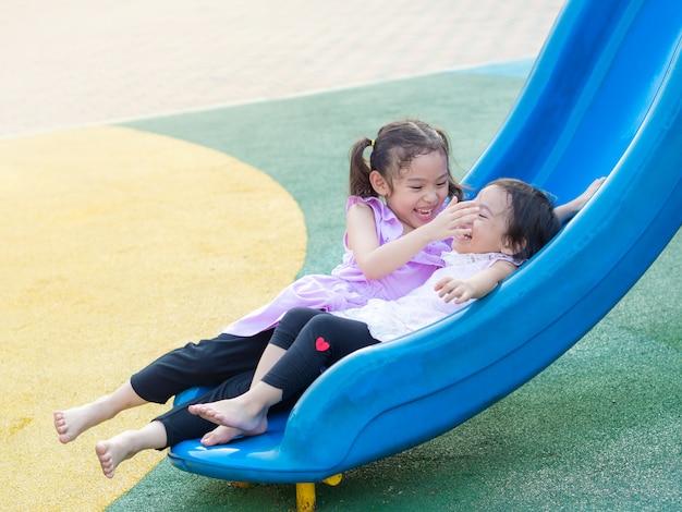 Lustiges kleines nettes mädchen zwei, das dia am spielplatz spielt. die ältere schwester kümmert sich um die jüngere schwester.