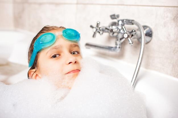 Lustiges kleines positives kaukasisches mädchen, das eine schwimmbrille trägt und im bad mit schaum spielt, während es auf entspannung am meer wartet. konzept der hygiene und home entertainment für kinder