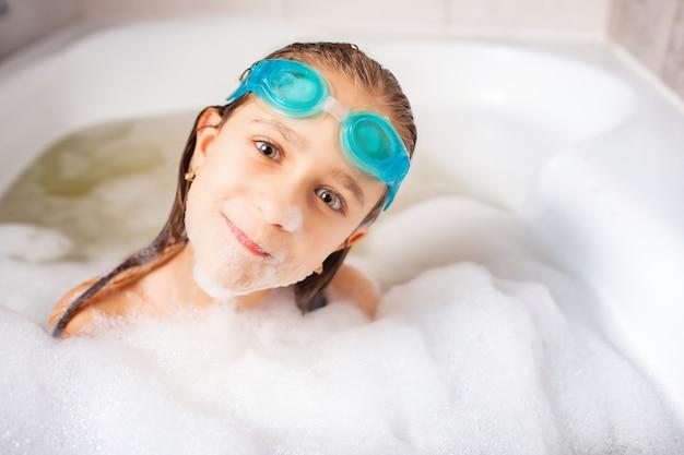 Lustiges kleines positives kaukasisches mädchen, das schwimmbrille trägt und im bad mit schaum spielt.