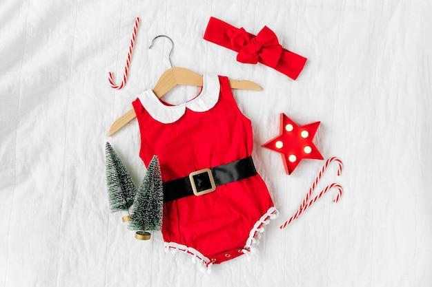 Lustiges kleines weihnachtsmannkostüm für babymädchen auf dem bett. frohe weihnachten.